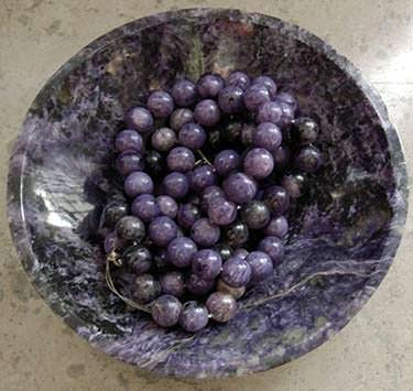 Charoite beads in a charoite bowl