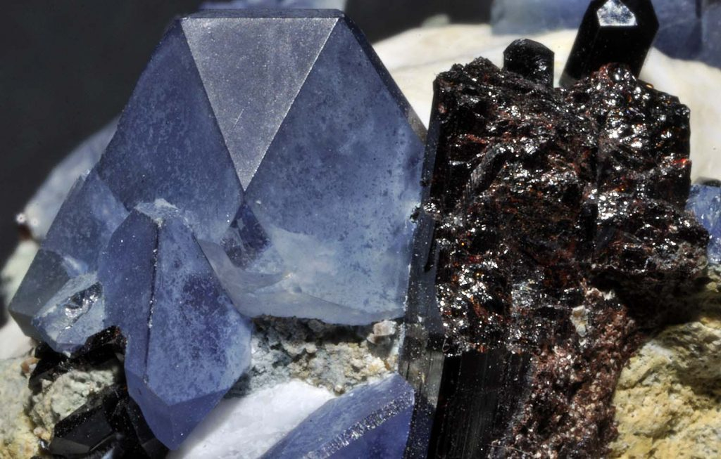 Benitoite crystals (left) next to neptunite crystals