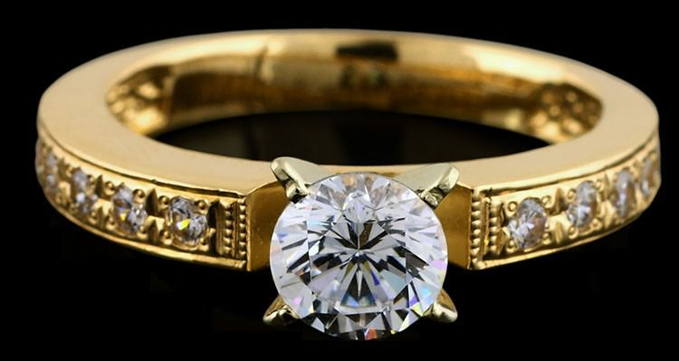 Solitaire diamond engagement ring with semi-channel set diamonds in yellow gold