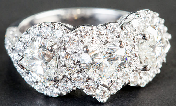 Three stone engagement ring with heart diamonds and halo
